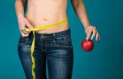 Geeigneter weiblicher Körper mit Apfel und messendem Band Gesunde Eignung und Essen, Diätlebensstilkonzept Lizenzfreie Stockfotografie