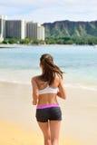 Geeigneter weiblicher Sportläufer des Active, der auf Strand rüttelt Stockfotografie