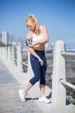 Geeignetes blondes Hören Musik auf dem Pier Lizenzfreies Stockfoto