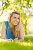 Geeignetes blondes Lügen auf dem Gras Lizenzfreies Stockbild