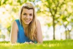 Geeignetes blondes Lügen auf dem Gras Stockfotografie