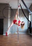 geeignetes blondes Mädchen, das eine Bremsung auf Mast tut Stangentanztraining Rote Spitze und Schlüpfer an und rote hohe Absätze stockfotos