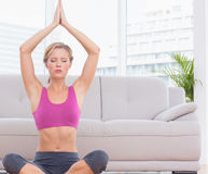 Geeignetes blondes Meditieren in der Lotoshaltung mit den Armen angehoben Stockbilder