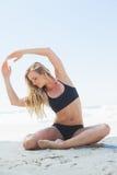 Geeignetes blondes Sitzen in der Yogahaltung auf dem Strand Stockbild