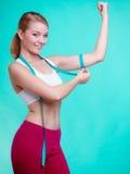 Geeignetes Mädchen der Eignungsfrau mit dem Maßbandmessen ihr Bizeps Stockfoto