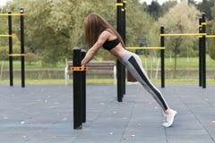 Geeignetes Mädchen, welches die Plankenübung im Freien am warmen Sommertag des Parks tut Konzept von Ausdauer und von Motivation Stockfotografie