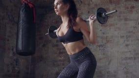 Geeignetes schönes Mädchen in der schwarzen Sportkleidung, die Hocken mit Barbell auf dem Hintergrund einer Backsteinmauer tut stock video footage