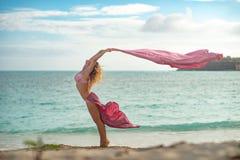 Geeignetes und sportliches junges M?dchen, das auf einem Strand mit rosa fliegender Seide aufwirft stockfotografie