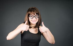 Χαμογελώντας geek κορίτσι στα γυαλιά με τους αντίχειρες επάνω Ευτυχής γυναίκα νικητών nerd Στοκ Εικόνες