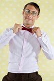 Geek Adjusting Bowtie. Portrait of a funny male geek adjusting bowtie over yellow textured background Royalty Free Stock Photos
