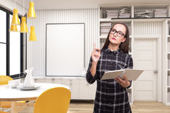 Geek girl with a book in a room with poster. Portrait of a geek girl with a book and wearing glasses and a checkered shirt standing in a room with yellow chairs Royalty Free Stock Images