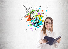 Geek girl and bright idea sketch. Portrait of a geek girl with a book wearing glasses and standing near a concrete wall with a colorful light bulb sketch above stock image