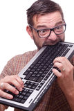 Geek is hysterically biting the keyboard Royalty Free Stock Image