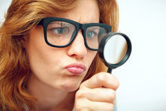 Geek looking through magnifying glass. Royalty Free Stock Photos