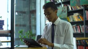 Geek mixed-race male student doing homework online, using tablet pc at library