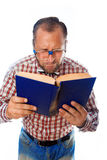 Geek with poor eyesight reading a book Stock Photography
