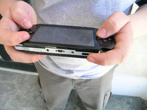 Geek with portable game device Royalty Free Stock Photography