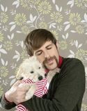 Geek retro man holding dog silly on wallpaper Royalty Free Stock Photography