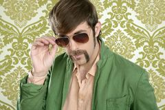 Geek retro salesperson man funny mustache. Sunglasses in green wallpaper royalty free stock images