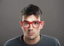 Geek. Teenage boy in red-framed eyeglasses looking at camera stock photography