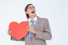 Geeky biznesmen uśmiecha się serce kartę i trzyma Fotografia Stock