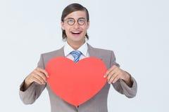 Geeky biznesmen uśmiecha się serce kartę i trzyma Fotografia Royalty Free
