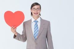 Geeky biznesmen uśmiecha się serce kartę i trzyma Zdjęcie Stock