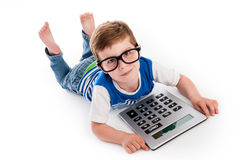Geeky Boy with Big Claculator. Geeky toddler boy lying on the floor with big calculator and big geeky glasses. Studio shot  on white Stock Image