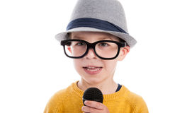 Geeky Boy with Microphone. Geeky toddler boy talking in a microphone,  wearing big glasses and a hat. Studio shot isolated on white Royalty Free Stock Images