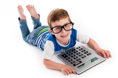 Geeky Boy Smiling with Big Claculator. Geeky toddler boy lying on the floor with big calculator and big geeky glasses. Studio shot  on white Royalty Free Stock Photos