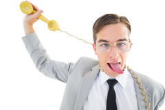 Geeky businessman being strangled by phone cord Stock Photo