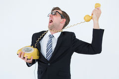 Geeky businessman being strangled by phone cord Stock Image