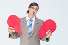 Geeky businessman crying and holding broken heart card Royalty Free Stock Images