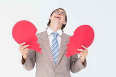 Geeky businessman crying and holding broken heart card Royalty Free Stock Photography