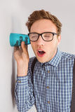 Geeky businessman eavesdropping with cup Royalty Free Stock Images
