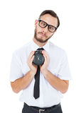 Geeky businessman holding alarm clock Royalty Free Stock Photography