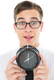Geeky businessman holding alarm clock Royalty Free Stock Image