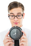 Geeky businessman holding alarm clock Royalty Free Stock Photos