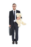 Geeky businessman holding briefcase and teddy Stock Images