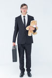 Geeky businessman holding briefcase and teddy Stock Photo