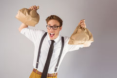 Geeky businessman holding paper bags Stock Image