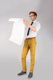 Geeky businessman reading large page Stock Images