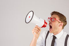 Geeky businessman shouting through megaphone Stock Image