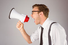 Geeky businessman shouting through megaphone Royalty Free Stock Photography
