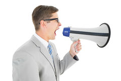 Geeky businessman shouting through megaphone Royalty Free Stock Image