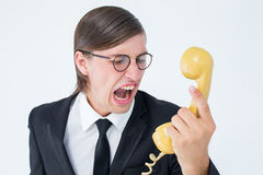 Geeky businessman shouting at retro phone Royalty Free Stock Image