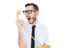 Geeky businessman shouting at telephone. On white background Stock Photo