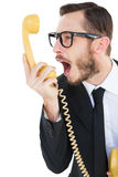 Geeky businessman shouting at telephone. On white background Royalty Free Stock Photo