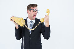 Geeky businessman shouting at telephone. On white background Stock Images