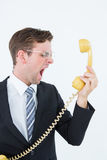 Geeky businessman shouting at telephone. On white background Royalty Free Stock Photography